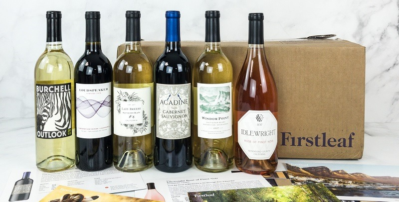 Six bottles of wine on a marble table stand in front of a large cardboard box. The box shows the Firstleaf wine subscription logo.